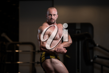 Man Standing Strong In The Gym And Flexing Muscles - Muscular Athletic Bodybuilder Fitness Model Posing After Exercises