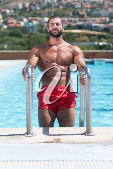 Portrait Of A Happy Attractive Muscular Man Posing In Swimming Pool