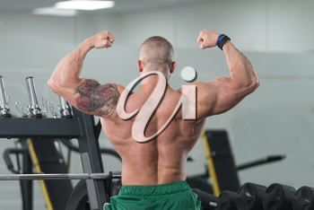 Healthy Young Tattoo Man Standing Strong In The Gym And Flexing Muscles - Muscular Athletic Bodybuilder Fitness Model Posing After Exercises