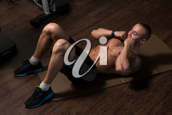 Young Man Performing Abdominals Exercising On Floor In A Fitness Club