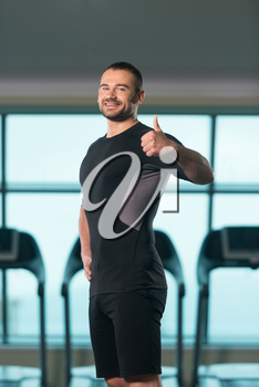 Handsome Personal Trainer Showing Thumbs Up Sign In A Fitness Center Gym Standing Strong