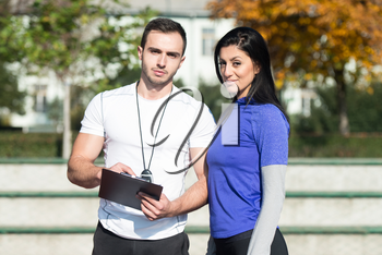 Personal Trainer Takes Notes While Young Woman Exercise in City Park Area - Training and Exercising for Endurance - Healthy Lifestyle Concept Outdoor