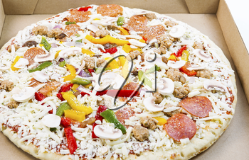 Horizontal photo of raw pizza, with lots of fresh ingredients,  in cardboard box