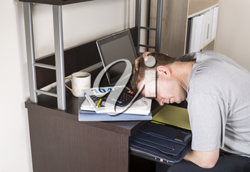 Mature man resting head on computer with calculator, tax income booklet and coffee cup on desk