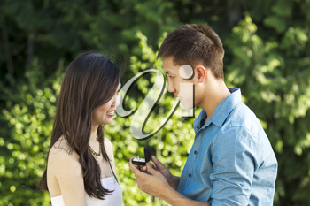 Horizontal photo of a young adult man proposing to his lady by showing her an engagement ring with blurred green trees in background