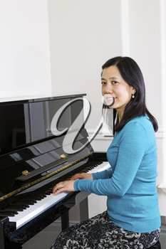 Vertical photo of mature woman playing piano with white walls in background