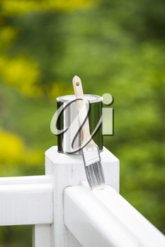 Vertical photo of used paint can and brush on white wood deck railing with a green nature background