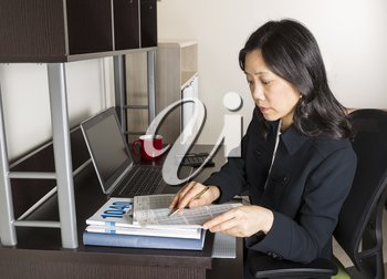 Professional Mature Asian woman  doing income taxes with tax form booklet, calculator, coffee cup and computer on desk