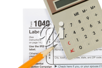Horizontal photo of United States Tax Form 1040 for Individual Income with Calculator and pencil isolated on white