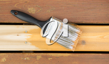 Horizontal photo of a large nylon paint brush on top of new wood board showing cedar stain color next to faded wood on outdoor deck