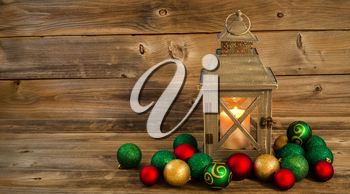 Horizontal front view of an old Asian design lantern and white candle glowing brightly inside with Christmas Ornaments on rustic wood