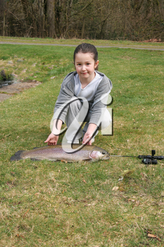 Vertical photo of young girl proudly displaying her large fish while kneeling on the ground
