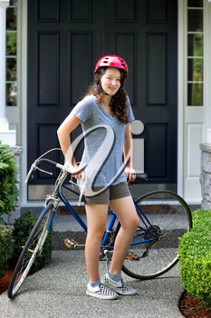 Vertical image of teenage girl, looking forward, while resting against her bicycle with home in background