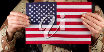 Close up horizontal image of United States of America flag with armed male soldier holding it while on black background.