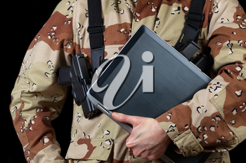 Close up horizontal image of laptop computer with armed male soldier holding it while on black background.
