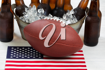 Close up of American football, ice cold beer in bucket, and flag with rustic white wood underneath. Perfect for the Fourth of July holiday. Filled frame in horizontal format.