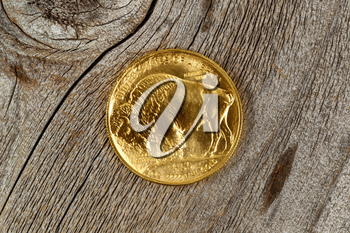 Reverse side of American Gold Buffalo coin, fine gold, on rustic wood.