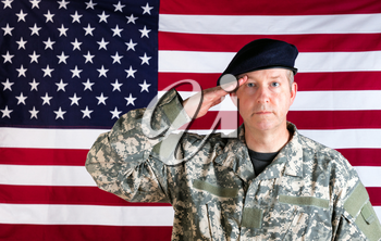 Veteran soldier, facing forward, saluting with USA flag in background.