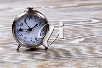 Retro table clock on faded white wooden boards.