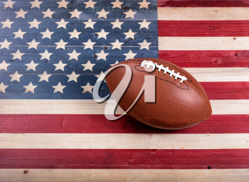 Top view of American football on rustic wooden boards with painted USA Flag.