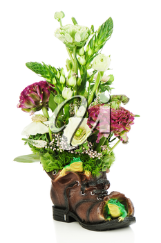 Flower bouquet arrangement centerpiece in old shoe with frogs isolated on white background.