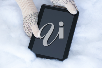 Woman hands in light teal knitted mittens are holding modern tablet pc on snow background. Winter concept.