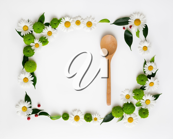 Wooden ladle and space for your text or product with decoration of chrysanthemum flowers and ficus leaves on white background. Overhead view. Flat lay.