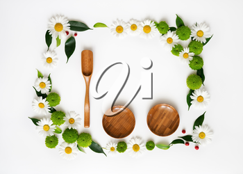 Wooden scoop, plates and space for your text or product with decoration of chrysanthemum flowers and ficus leaves on white background. Overhead view. Flat lay.