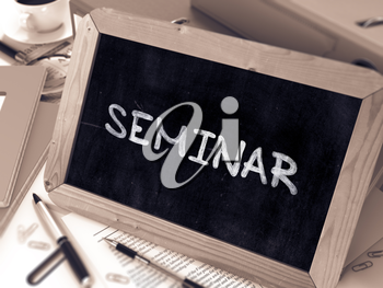 Seminar Handwritten by White Chalk on a Blackboard. Composition with Small Chalkboard on Background of Working Table with Office Folders, Stationery, Reports. Blurred, Toned Image. 3D Render.