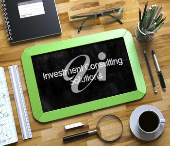 Investment Consulting Solutions on Small Chalkboard. Investment Consulting Solutions - Green Small Chalkboard with Hand Drawn Text and Stationery on Office Desk. Top View. 3d Rendering.
