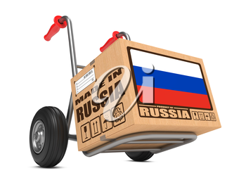 Cardboard Box with Flag of Russia and Made in Russia Slogan on Hand Truck White Background. Free Shipping Concept.