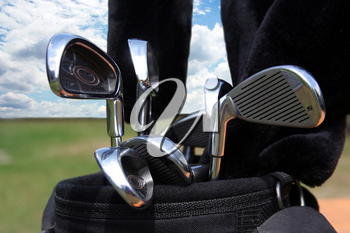 Golf bag with clubs against a beautiful blue sky
