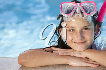 A cute happy young girl child relaxing on the side of a swimming pool wearing pink goggles and snorkel