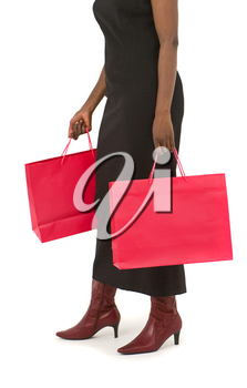 Studio shot of an African American woman clutching full red shopping bags. Isolated on a white background with a shadow for depth.