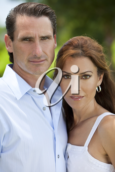 Portrait shot of an attractive, successful and happy middle aged man and woman couple in their thirties, shot outside in natural light.