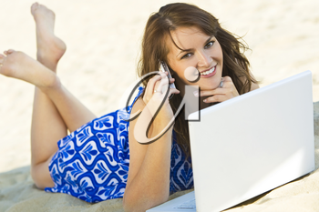 A sexy and beautiful young brunette woman using her laptop and cell phone on the beach
