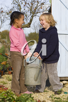 Two young children carrying a heavy watering can in an Autumnal garden