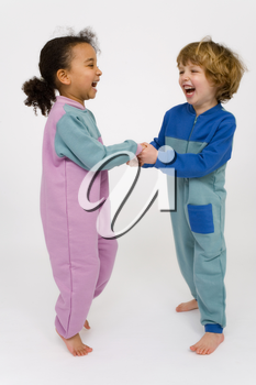 Two young children, one a mixed race little girl the other a blonde boy, holding hands and bouncing around having fun