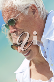 Happy senior man and woman couple together looking out to sea on a deserted tropical beach