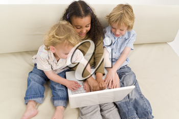 Three young children using a laptop together while sitting on a settee