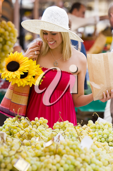 A beautiful young woman shopping for fruit in a market