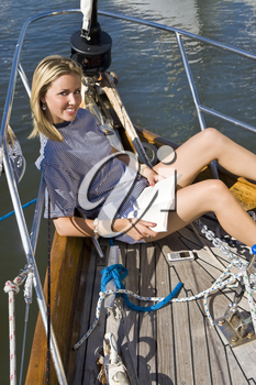 A stunningly beautiful young woman relaxing on the deck of a yacht with a book and her mobile phone.
