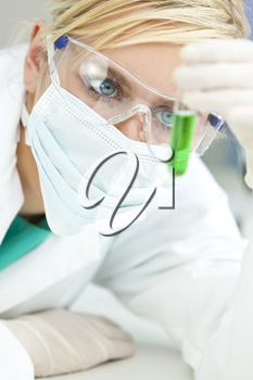 A blond medical or scientist researcher or doctor looking at a test tube of green solution in a laboratory while wearing safety glasses, surgical face mask and gloves.