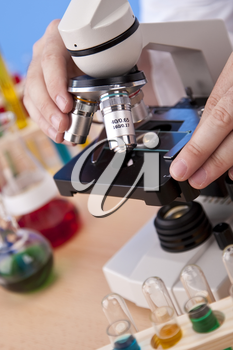 A medical or scientific researcher using a microscope in a laboratory environment
