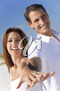 Attractive middle aged man and woman romantic couple in white clothes holding hands to camera on a tropical beach with bright clear blue sky