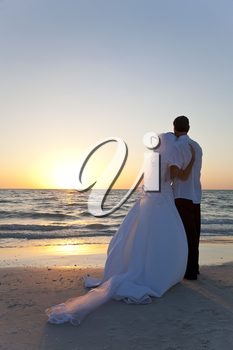Wedding of a married couple, bride and groom, together at sunset on a beautiful tropical beach