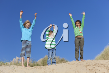 Three children, two blond boys and a mixed race little girl, having fun arms raised in the dunes of a sandy beach