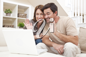 Happy man and woman couple in their thirties, sitting together at home on a sofa using a laptop computer to make a VOIP internet phone call and waving at the screen