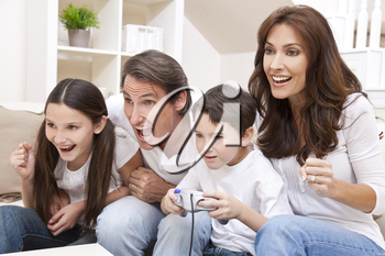 Happy family, parents, son and daughter, having fun playing video console games together, the young boy has the handset controller everyone else is cheering.