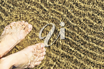 Bare feet wading in clear shallow water at sandy beach